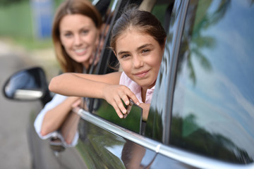Woman and kid looking by car window