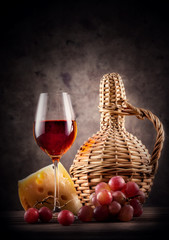 Glass of red wine with decanter and grapes