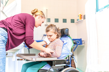 Disability a disabled child being cared for together with a nurse using special needs equipment / Disability a disabled child being cared for