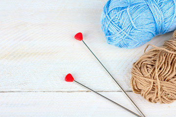colorful yarn for knitting with spokes on white wooden background