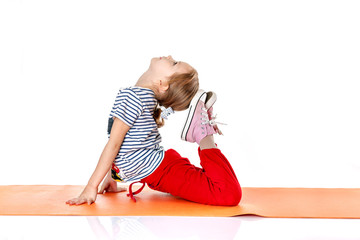 little girl doing gymnastic exercises on an orange yoga mat