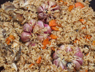 The preparation of traditional Uzbek pilaf with meat, carrots, garlic and spices