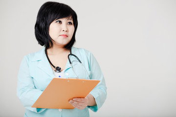 Young female Asian doctor with stethoscope standing still, think