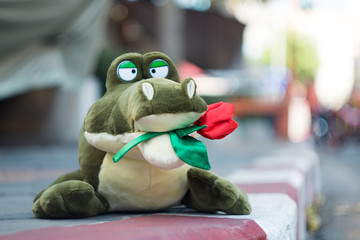 stuffed alligator Holding roses on the road