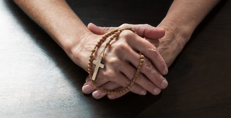 talking hands concept - female hands holding tight a Christian cross praying for confession on dark wooden table,studio shot
