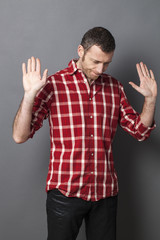 negligence concept - resigned 40s man expressing carefree responsibility for childish mistake,studio shot