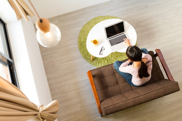 Top view of woman using computer for working at home