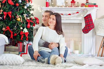 Happy Family lying on carpet, on Christmas tree background