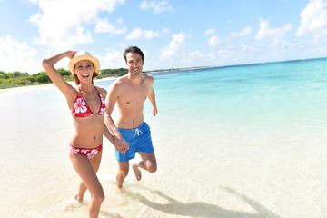Cheerful couple running on a white sandy beach