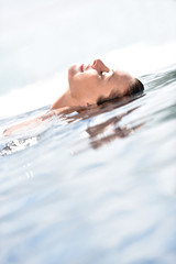 Beautiful woman relaxing on the edge of infinity pool