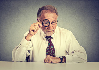 Senior business man looking through a magnifying glass sitting at office desk