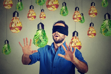 Blindfolded man walking through light bulbs shaped as junk food and green vegetables