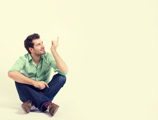 happy man in green shirt and blue jeans sitting on the floor pointing at blank copy space