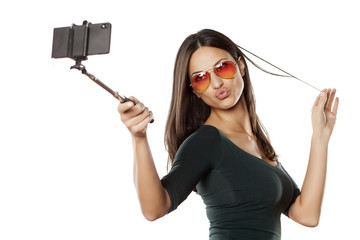 pretty brunette with sunglasses takes a selfies with monopod
