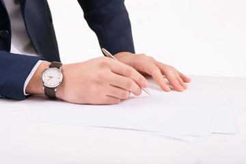 Businessperson writing on paper.