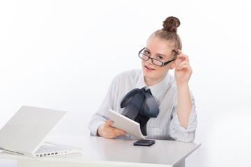 fröhliche junge Frau im Büro mit Laptop, Schreibblock und Brille