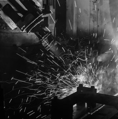Welding robots movement in a car factory black white