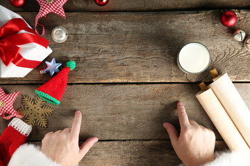 Christmas concept. Santa Claus hands, gift box, toys, glass of milk on wooden table, close up