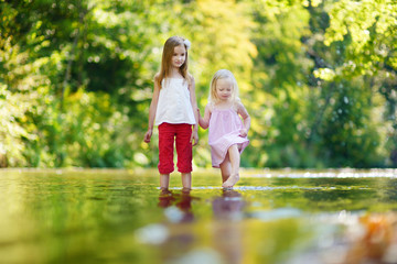 Two cute little girls having fun by a river on warm summer day