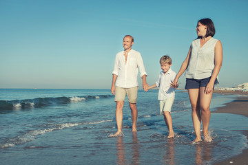 Happy family walk together on the sea surf line