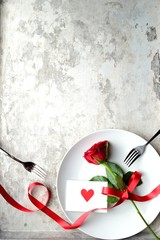 Red rose with red heart message card on the white dish