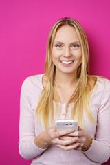 junge blonde frau mit ihrem smartphone vor rosa hintergrund