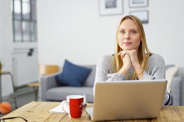 junge frau sitzt entspannt zu hause am tisch mit ihrem laptop