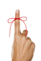 index finger tied with a red rope