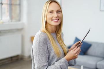 lächelnde frau arbeitet zuhause mit ihrem tablet