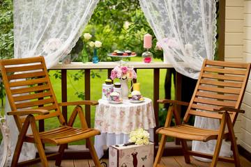 Стол с пирожными, чайными чашками, букетом, накрытый на двоих на террасе