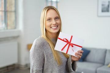 lächelnde frau mit einem geschenk-gutschein in ihrer wohnung