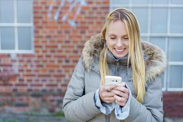 glückliche junge frau schaut draußen auf ihr smartphone