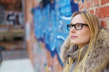 junge kreative frau lehnt an einer backstein-wand