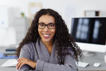 lächelnde frau sitzt im büro mit computer im hintergrund