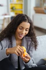 junge frau schält eine mandarine