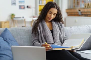 frau lernt zuhause mit computer und unterlagen