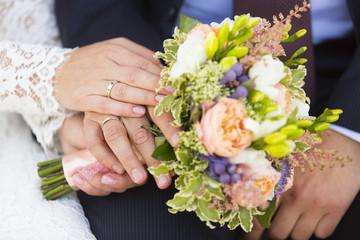 Руки жениха и невесты с обручальными кольцами на свадебном букете