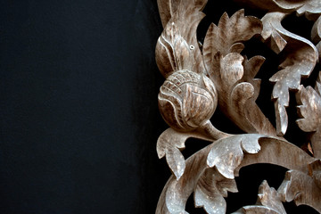 Thai wood carving of flowers on a black background