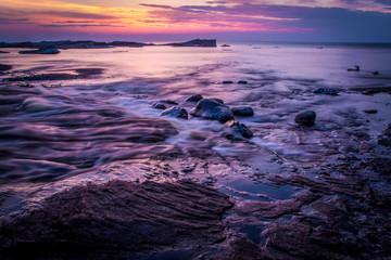 Lake Superior Sunset Background. The sun sets over the Lake Superior coast with iceberg islands floating at the horizon. Pictured Rocks National Lakeshore. Munising, Michigan.