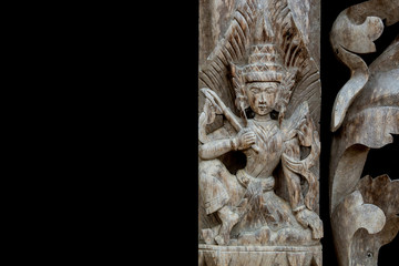 Thai wood carving of divine on a black background