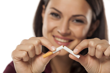happy young woman breaking a cigarette