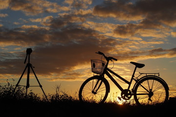 A tripod and a bicycle on country road in the evening: silhouette photo