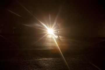 A shadowy figure standing in front of vehicle headlights in the dark of night.