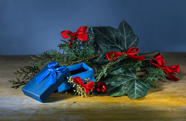 traditional christmas composition with an open gift box, ivy leaves and small red bows