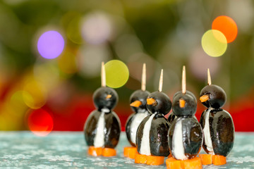 Penguins made of black olives, carrots and feta cheese, against festive background