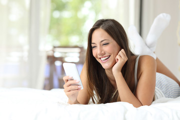 Girl using a mobile phone on the bed at home