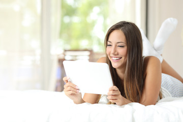 Girl watching videos in a tablet on the bed