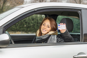 girl in the car smiling happy showing her driver's license - caucasian people