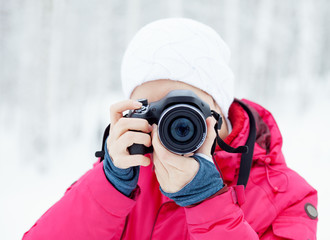 The girl with the camera on the background of winter snow.