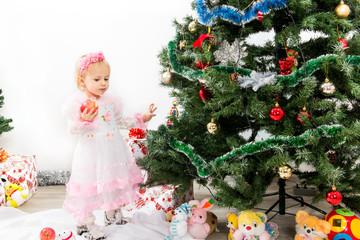 Little girl near the Christmas tree eats an apple